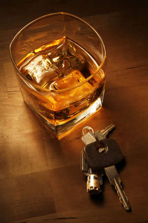 Whiskey in light pool on brown table with car keys