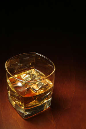 nightcap: Whiskey in light pool on brown table with copyspace