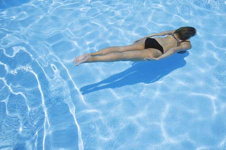 underwater woman: Pretty girl in bikini diving into blue pool