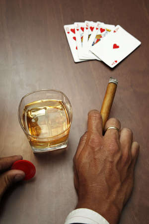 Poker player with cards cigar and whiskey  Editorial