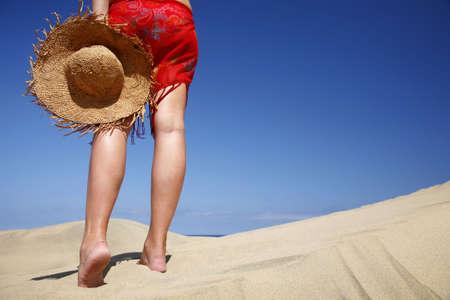 beachcomb: Woman walking across a sandy beach with a satraw hat