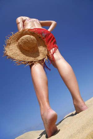 beachcomb: Woman walking across a sandy beach with a straw hat Stock Photo