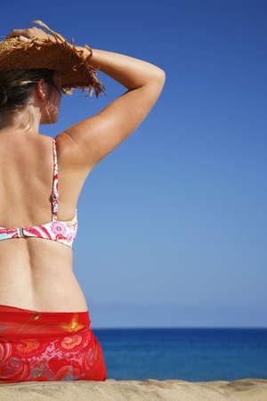 beachcomb: Woman sitting on empty sand beach with blue sky