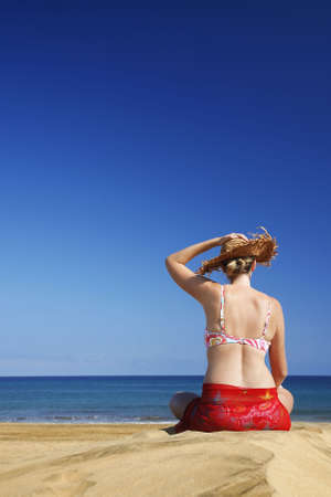 beachcomb: Woman sitting on empty sand beach with blue sky