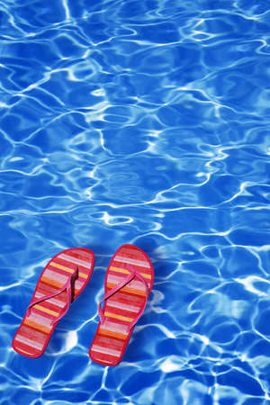 Bright blue pool water background with sandals photo