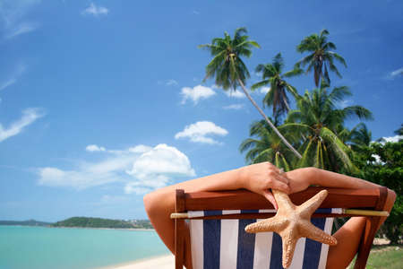 deckchair: Woman in deckchair with tropical view background