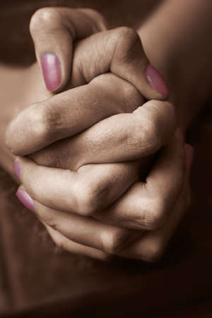 clasping: Sepia hands at prayer on a bible Stock Photo