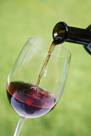 Red wine pouring into glass with nice green background photo