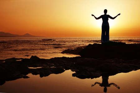Woman doing yoga at sunset on the seashore photo