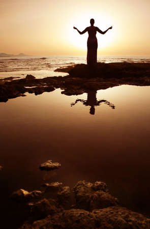 Woman in meditation pose at sunset with reflection in water photo