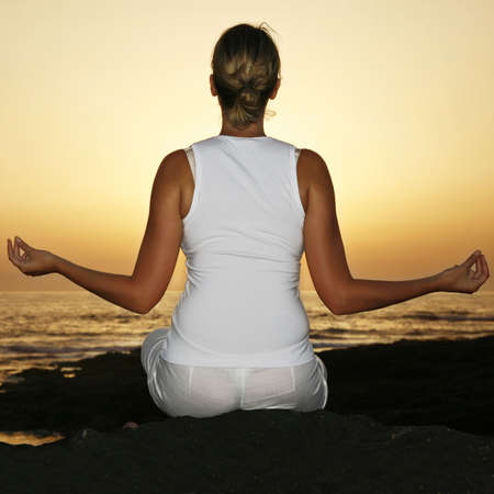 Woman in meditation pose at sunset with fill flash photo