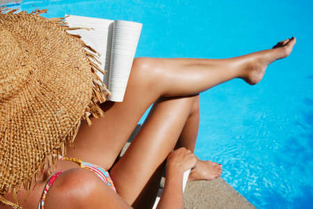Pretty girl in sunhat reading by blue pool photo