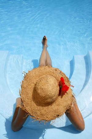 descansando: Mujer en azul se extiende piscina
