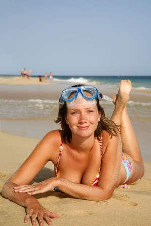 Pretty girl sunbathing on golden beach