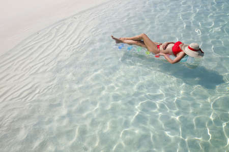 lilo: Woman floating on lilo in tropical lagoon Stock Photo