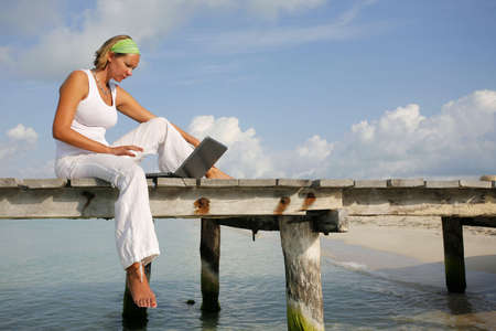 Woman in white looking at a laptop on a tropical boardwalk Stock Photo