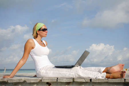 Woman in white looking at a laptop on a tropical boardwalk photo