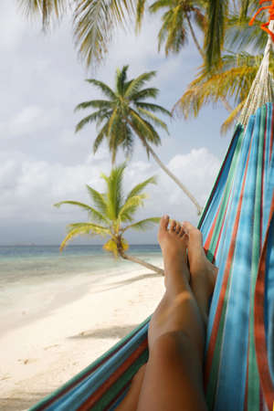 siesta: Woman in a hammock on a tropical beach