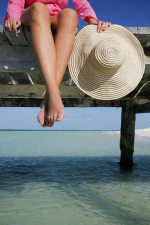 Womans feet and hat with jetty Stock Photo