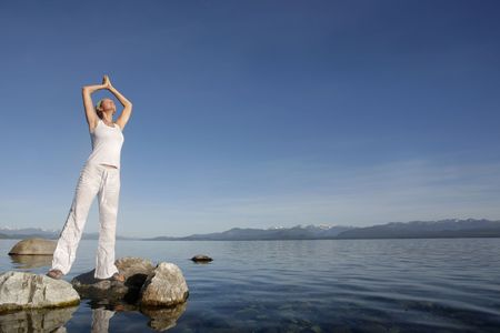 Attractive woman in white meditating by still water Stock Photo