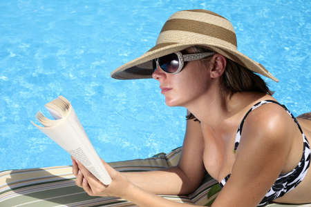 Woman reading by the swimming pool Stock Photo