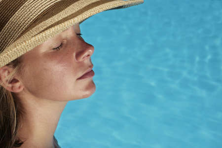 Woman sunbathing by blue swimming pool photo