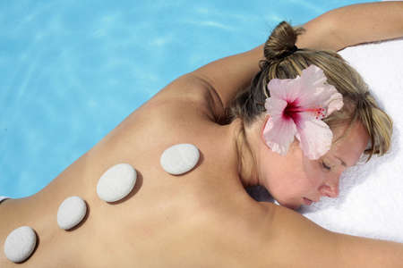 Woman with massage stones by a blue pool Stock Photo - 5035837
