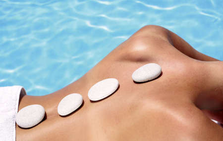 Woman with massage stones by a blue pool Stock Photo