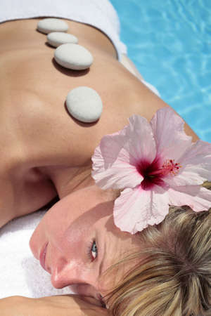 Woman with massage stones by a blue pool Stock Photo - 5035839