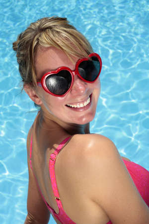 Woman in heart-shaped sunglasses besides a bright blue swimming pool Stock Photo - 5035853