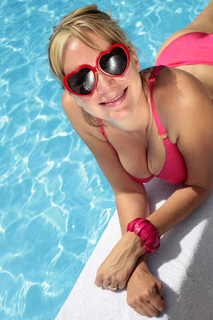 Woman in heart-shaped sunglasses besides a bright blue swimming pool Stock Photo - 5035846