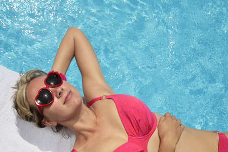 Woman in heart-shaped sunglasses besides a bright blue swimming pool photo