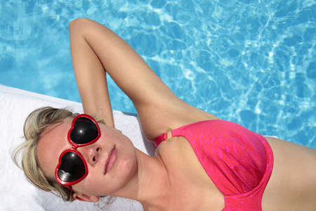 Woman in heart-shaped sunglasses besides a bright blue swimming pool Stock Photo - 5035861