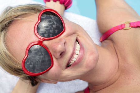 heartshaped: Woman in heart-shaped sunglasses besides a bright blue swimming pool