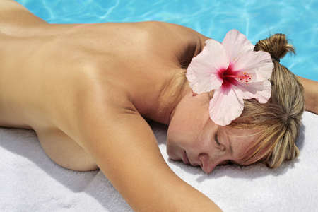 Woman with massage stones by a blue pool Stock Photo - 5035860