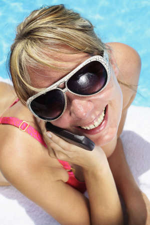 Woman in sunglasses besides a bright blue swimming pool talking into her mobile phone photo