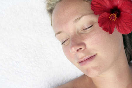 Woman relaxing with a red flower photo