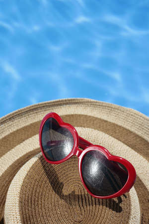 Red Heart-shaped Sunglasses and Hat by a Blue Pool Stock Photo - 5060473