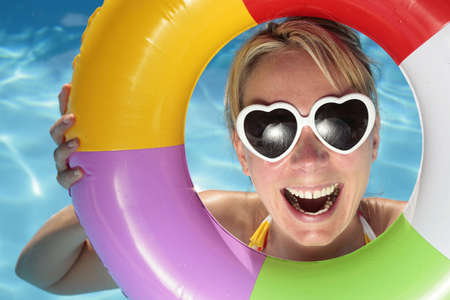 Laughing woman with sunglasses and inflatable toy photo