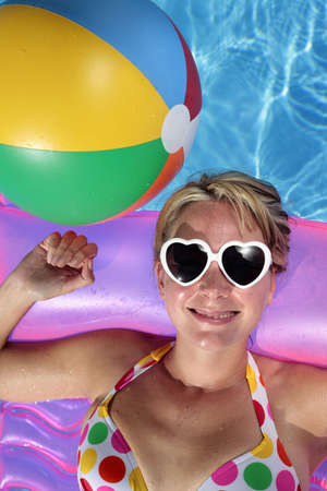 Laughing woman with sunglasses and inflatable toys photo
