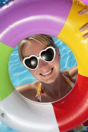 Laughing woman with sunglasses and inflatable toy Stock Photo