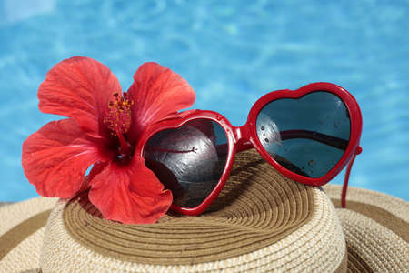 informal clothing: Fuky sunglasses on a summer hat with a red tropical hibiscus flower and nice blue pool water