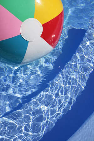 Multicolored Beachball in a beautiful blue swimming pool photo