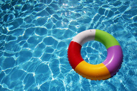 Inflatable Rubber Ring floating in a beautiful blue pool Stock Photo