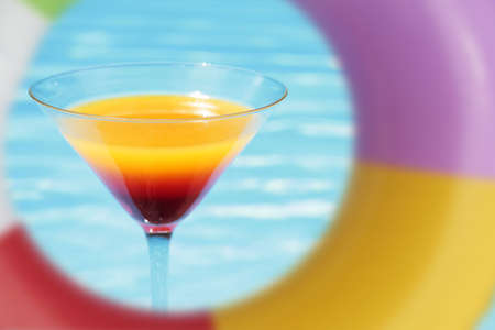Colorful cocktail in front of attractive blue pool water
