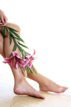 reflexology: Legs and pink lillies over a bright background Stock Photo