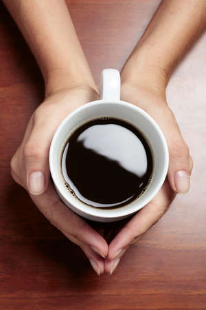 Womans hands holding a cup of coffee on a dark table