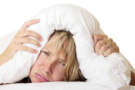 Woman ith her head under her pillow trying to sleep photo