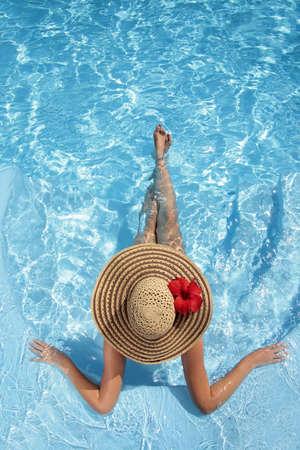 бассейн: Женщина, сидящая в бассейне в большом Sunhat