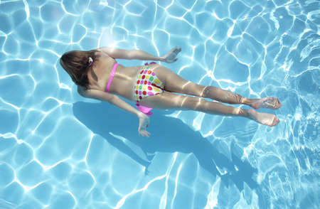 Woman in a polka dot bikini swimming underwater
